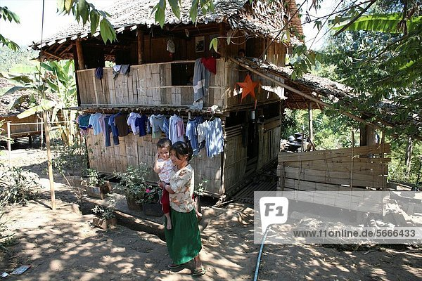 A Burmese woman holds her child outside her hut in the displaced persons camp near Thailand In Myanmar Burma  thousands of people have settled near the border as a result of oppression in their homeland Around 200 Burmese displaced people have settled in