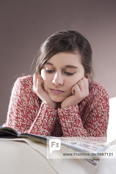 Teenagerin liest eine Zeitschrift auf der Couch