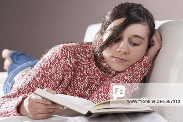 Teenagerin liest ein Buch auf der Couch