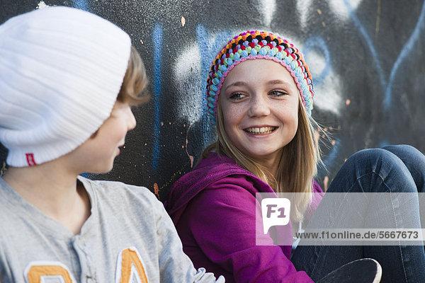 Teenagerin und Junge sitzen an einer Graffitiwand