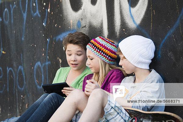Drei Teenager benutzen einen Tablet PC