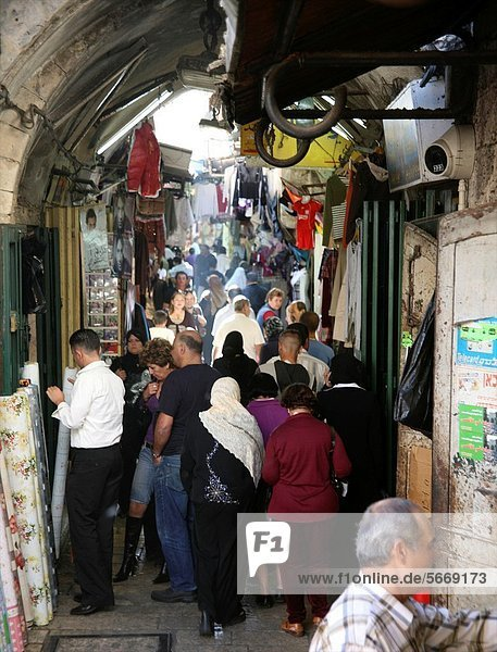 Crowds walk through a market in the old city section of Jerusalem