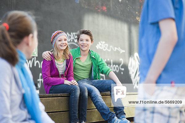 Lächelnder Teenager umarmt seine Freundin