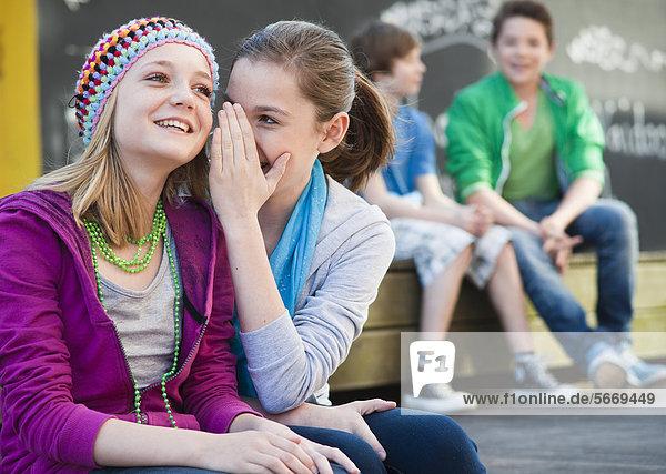 Zwei Teenagerinnen tuscheln mit zwei Jungen im Hintergrund