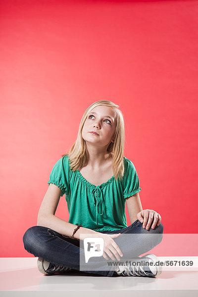 Nachdenkliche Teenagerin schaut nach oben