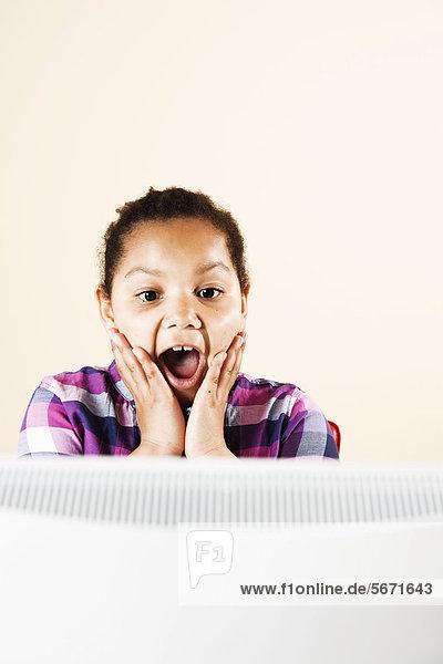 Überraschtes Mädchen schaut auf Computermonitor