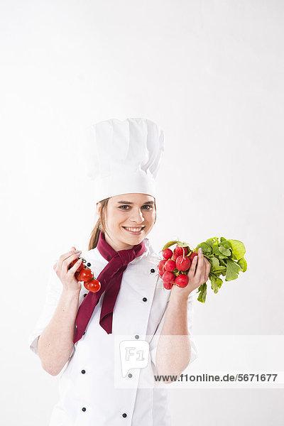 Lächelnde Köchin hält Tomaten und Radieschen Lächelnde Köchin hält Tomaten und Radieschen
