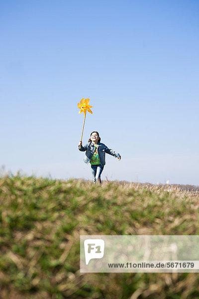 Mädchen rennt mit Windrädchen auf einer Wiese Mädchen rennt mit Windrädchen auf einer Wiese