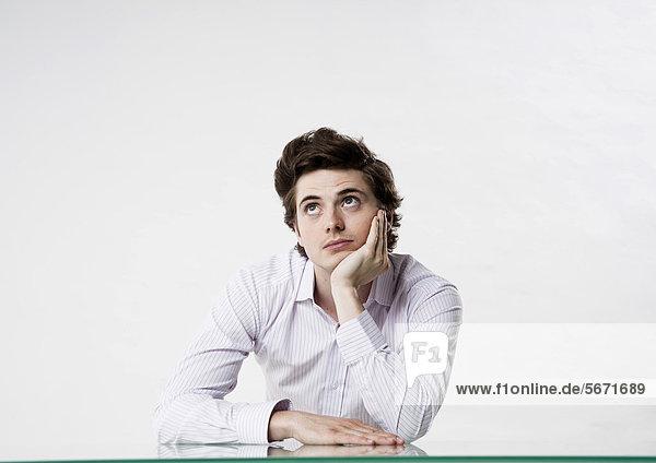 Junger Mann am Schreibtisch schaut nach oben