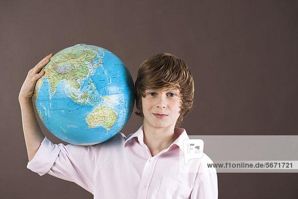 Teenager hält einen Globus