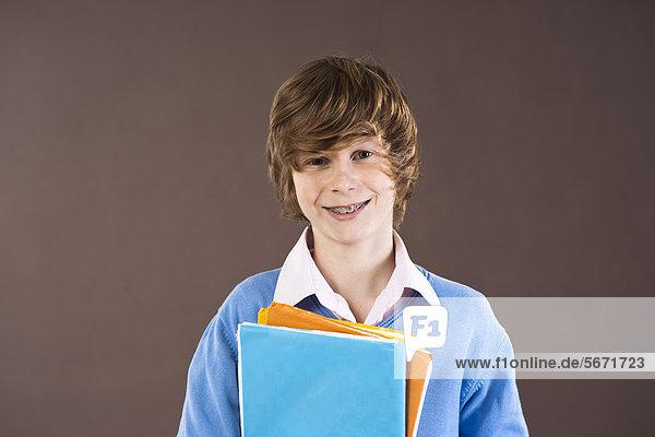 Lächelnder Teenager hält Mappen  Portrait