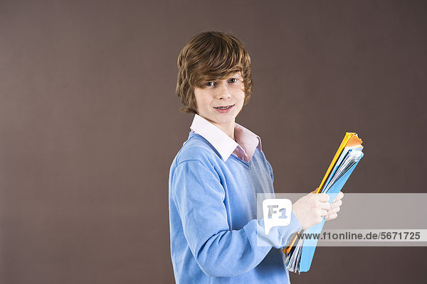 Lächelnder Teenager hält Mappen