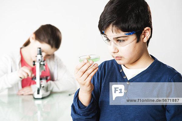 Teenager und Teenager mit Mikroskop und Schutzbrllle