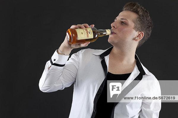 Junger Mann trinkt aus Whisky-Flasche
