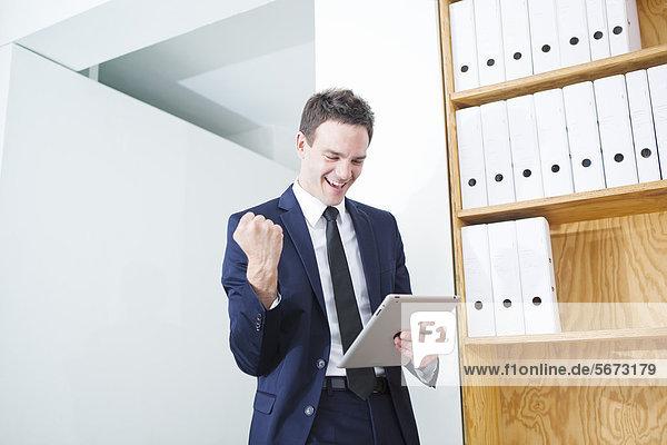 Jubelnder Geschäftsmann mit Tablet PC im Büro
