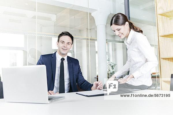 Geschäftsmann und Geschäftsfrau im Büro arbeiten mit Laptop