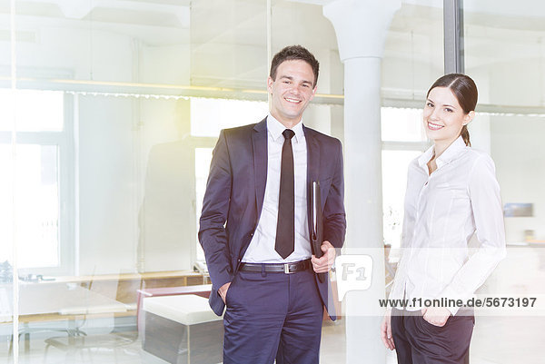 Smiling businessman and businesswoman in office