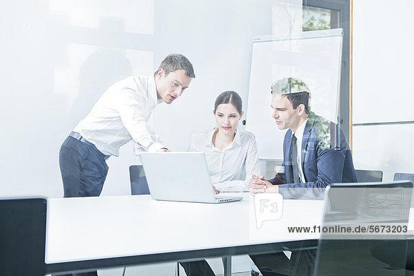 Drei Geschäftsleute arbeiten mit Laptop im Konferenzraum