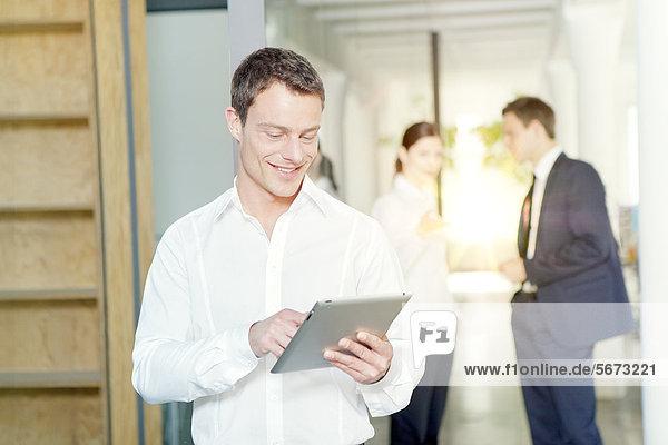Lächelnder Geschäftsmann mit Tablet-PC im Büro
