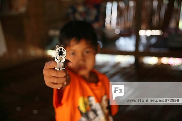 A young refugee aims a handgun at the camera Around 130 000 Burmese refugees have settled in Thailand due to opression in their homeland of Myanmar Burma Approximately 30 000 refugees now live in Mae Sot western Thailand and receive humanitarian aid Anoth