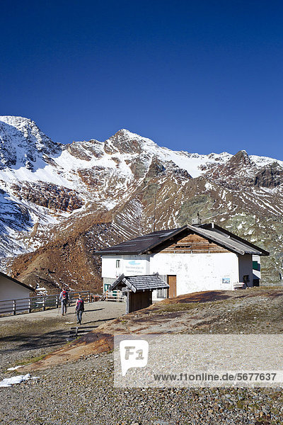 Wanderer beim Aufstieg zur hinteren Eggenspitz im Ultental oberhalb des Weißbrunnsees  hier bei der Höchster Hütte  hinten die Weißbrunnspitz  links der Gipfel der hinteren Eggenspitz  Südtirol  Italien  Europa
