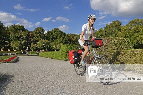 Frau fährt mit Reiserad durch den Hofgarten  München  OberBayern  Bayern  Deutschland  Europa