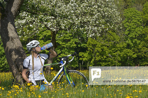 Radfahrerin macht Rast  Oberbayern  Bayern  Deutschland  Europa