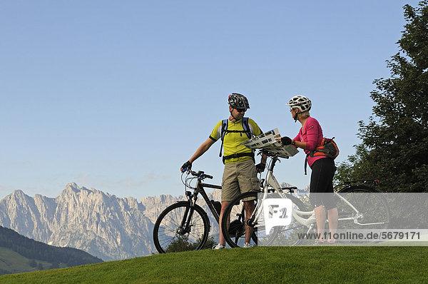 Paar mit Elektrofahrrädern vor dem Wilden Kaiser  Reit im Winkl  Chiemgau  Oberbayern  Bayern  Deutschland  Europa