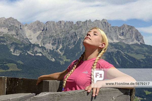 Wanderin sonnt sich  bei der Lederer Alm  Hartkaiser  Blick auf Wilder Kaiser  Tirol  Österreich  Europa