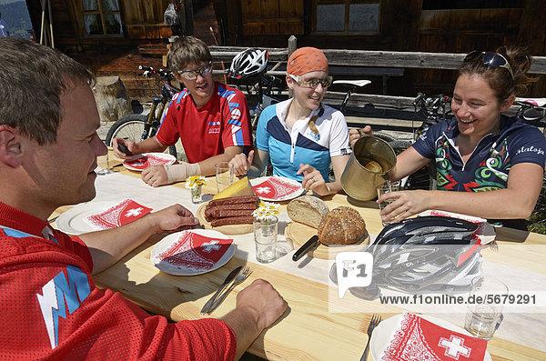 Mountain bikers having a Brotzeit  hearty snack  at Chumigalm alp  Uf de Fluene  Zweisimmen  Gstaad  Municipality of Saanen  Bernese Oberland  Switzerland  Europe