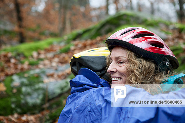 Mature couple wearing cycling helmets and embracing