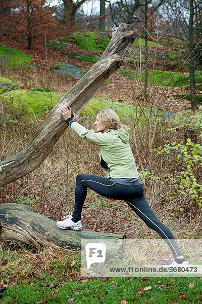 Reife Frau  die sich im Wald gegen einen Baum streckt.
