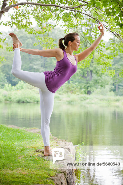 Mittlere erwachsene Frau beim Yoga natarajasana Pose am Fluss