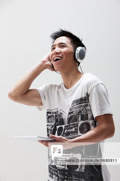 Junger asiatischer Mann mit digitalem Tablett mit Kopfhörer,  Studioaufnahme