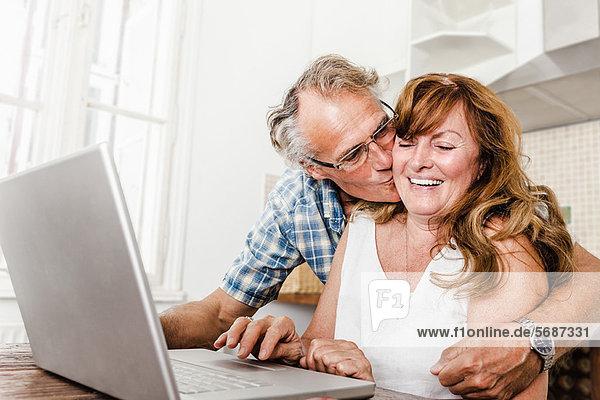 Älteres Paar mit Laptop in der Küche