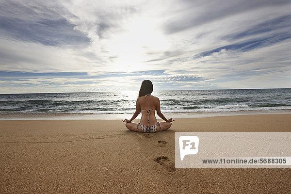 Frau meditiert am Sandstrand