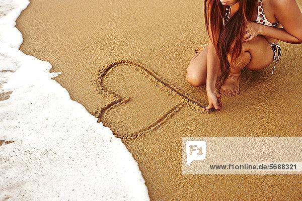 Teenagermädchen malt Herz im Sand