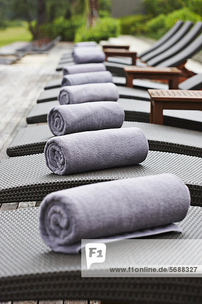 Rolled towels on lawn chairs outdoors