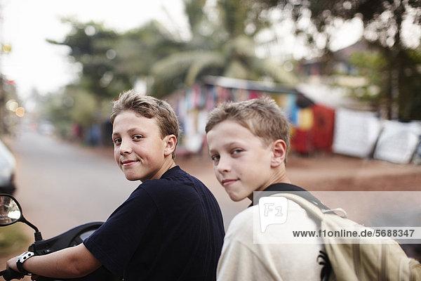 Teenager Jungen fahren Roller auf Schotterpiste