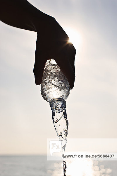 Teenager-Junge gießt Wasser aus der Flasche