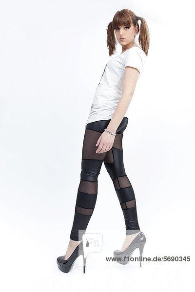 Junge Frau mit Zöpfen  weißem Shirt  halbtransparenten Leggins und High Heels
