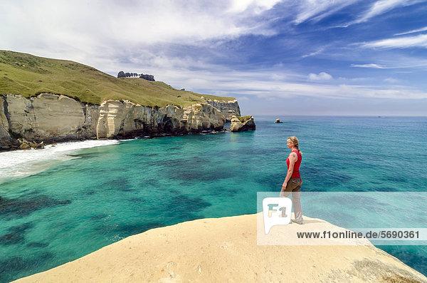 Frau steht an einer Klippe an der Steilküste beim Tunnel Beach nahe Dunedin  Südinsel  Neuseeland  Ozeanien