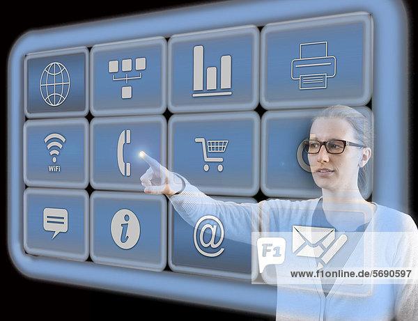 Frau bedient virtuelle Icons  interaktive Bedienoberflächen  Symbolbild virtuelles Arbeiten
