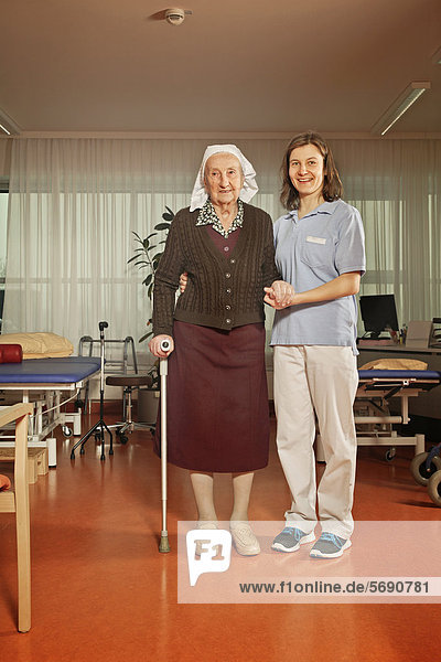 Alte Frau mit Physiotherapeutin