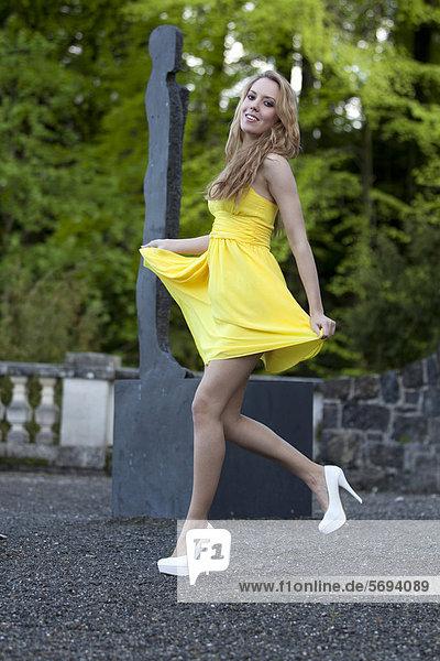 Junge Frau posiert in gelbem Kleid mit hohen weißen Schuhen