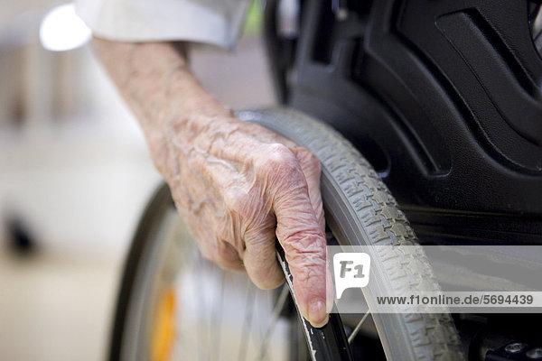 Seniorin  Detail Hand am Rollstuhl  im Seniorenheim