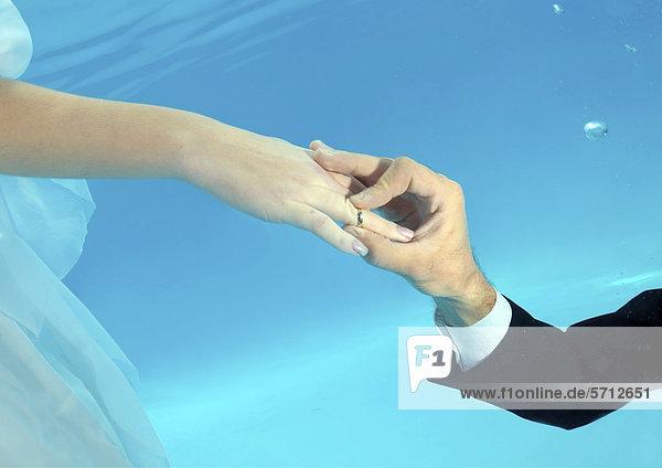 Hände von Braut und Bräutigam  Ringtausch  Unterwasser-Hochzeit in einem Pool  Odessa  Ukraine  Osteuropa