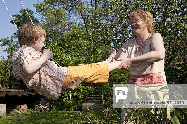 Frau schubst kleinen Junge auf einer Schaukel an