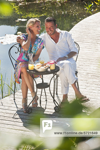 Österreich  Salzburger Land  Paar beim Frühstück auf der Brücke über den Teich
