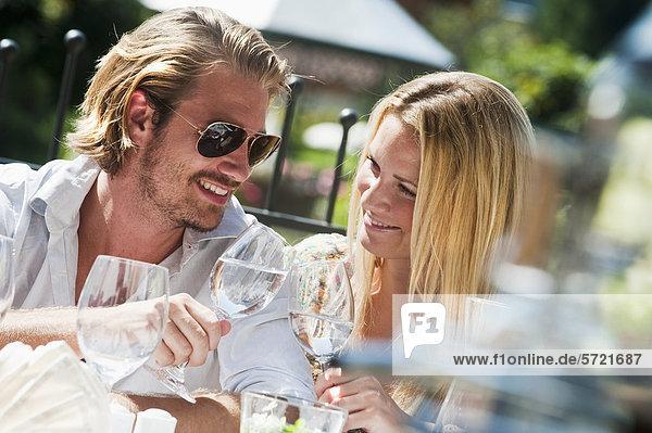 Österreich  Salzburger Land  Paar sitzend auf Terrasse im Hotelgarten